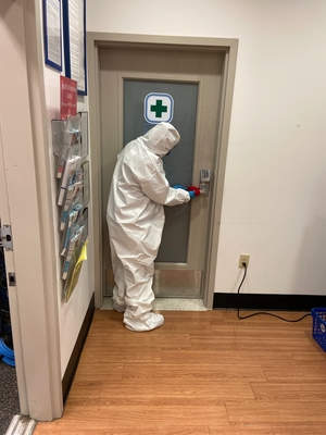 Rainbow International of Sugar Land and Katy service professional in hazmat suit cleaning a door handle