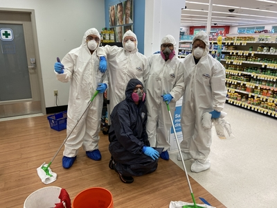 Rainbow International of Sugar Land and Katy service professionals in hazmat suits taking a group photo