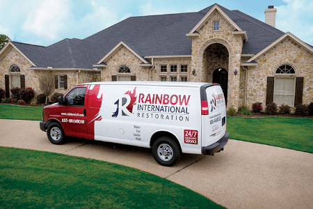 A Rainbow International van parked in front of a home.