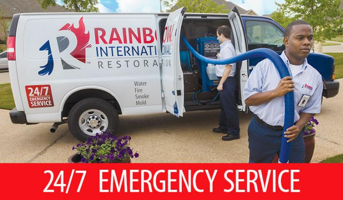 Rainbow International restoration professionals removing equipment from van
