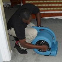 Photo of a techinician adjusting a water mitigation fan.
