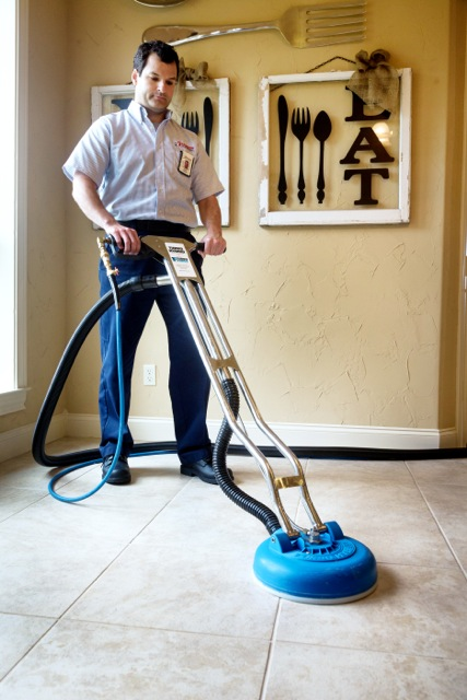 Service professional cleaning the tile grout in a home.
